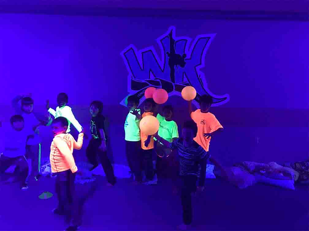 kids playing balloons wearing glow in the dark world karate fairfax's uniform